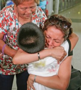 Filipina mother kissing son before departing at the airport for work in abroad